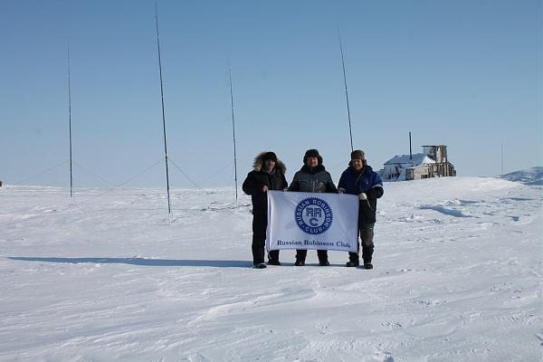 участники экспедиции с флагом RRC на фоне антенн